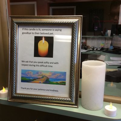 framed sign informing other clients that someone is saying goodbye to their pet when a candle is lit