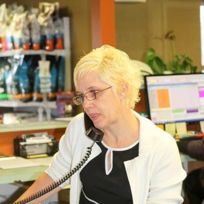 Blonde short haired team member speaking on phone at front desk. Team member is a woman and has on a black dress and glasses