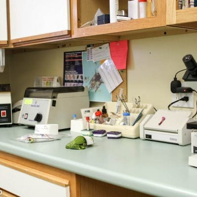 counter of back of office. on counter are several medical devices and supplies such as a microscope and test tubes